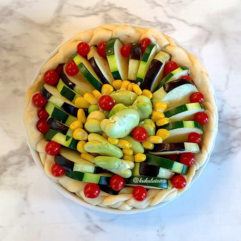 外側はコーン粒上に茄子→マイクロトマト→ズッキーニ→マイクロトマト→茄子の順に重ねて並べ、内側はコーン粒とそら豆をのせます